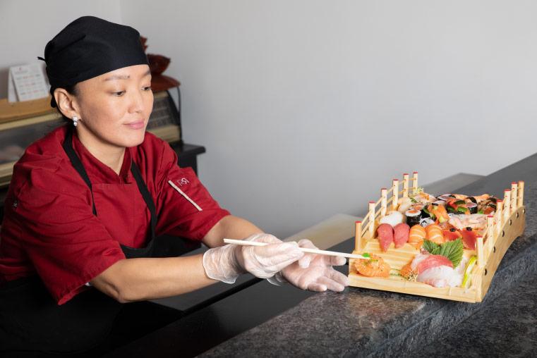gereltuya souriante, baguettes chinoises à la main, agence un plat de sushis