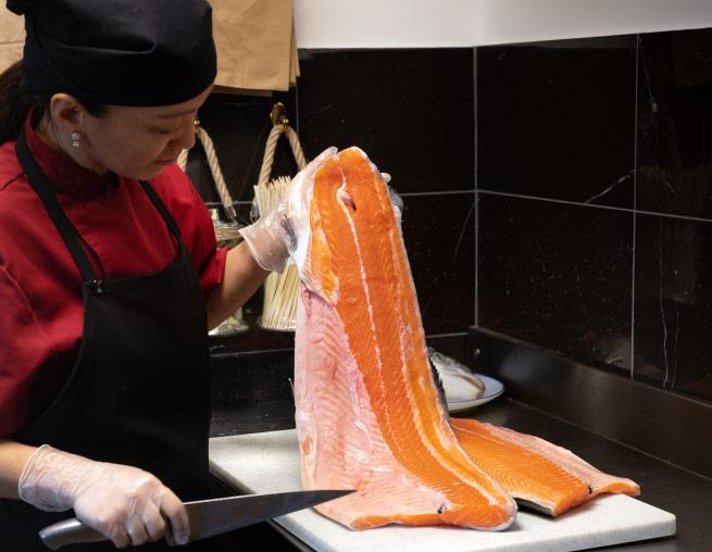une cuisinière avec un tablier noir tient à la main un immense filet de saumon.