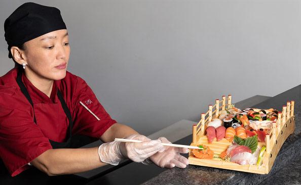 Une cuisinière asiatique prépare un plat à l'aide de baguettes