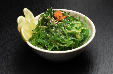 Bol avec salade d'algues vertes posé sur une table noire