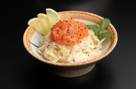 Salade de choux saumon dans un bol posé sur une table noire