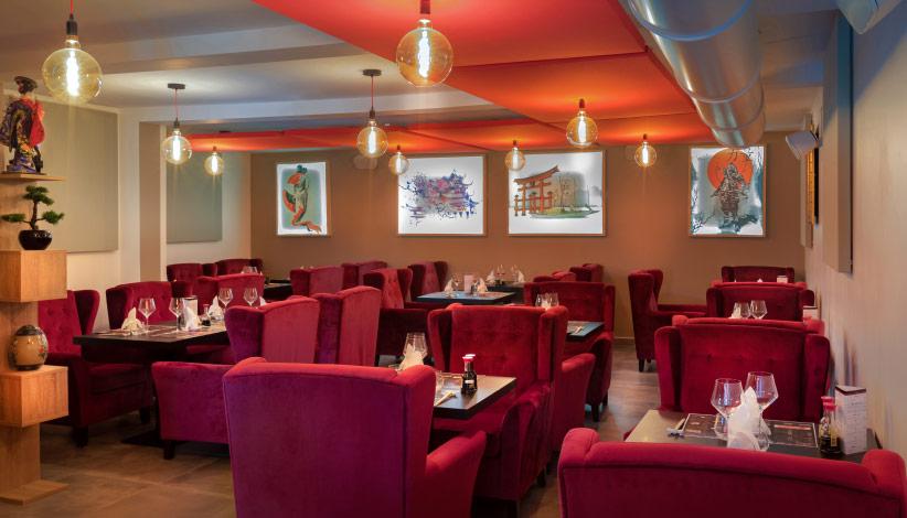 salle du restaurant du japon, avec de grands fauteuils rouges