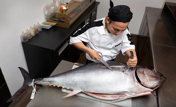 Découpage d'un thon entier par un cuisinier asiatique
