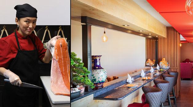 Comptoir de restaurant avec une cuisinière un filet de saumon à la main