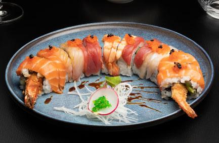 Assiette de futo maki composée de poissons et crevettes posée sur une table noire