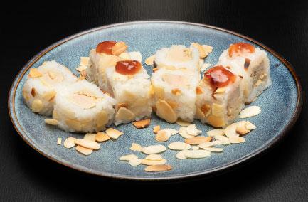 Assiette bleue avec des de futo makis au foie gras sur une table noire