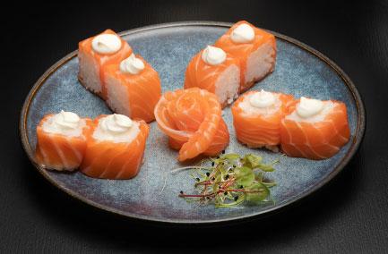 Assiette de naka makis au saumon sur une table noire
