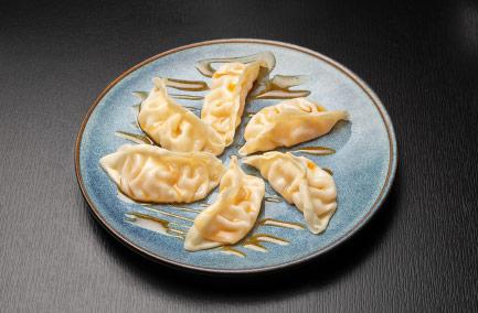 Assiette bleue avec six raviolis japonais sucrés dedans