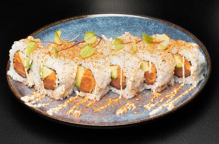 Assiette de futo makis saupoudrés d'épice jaune sur une table noire
