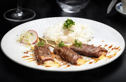 Trois brochettes de yakitori beuf fromage servies dans une assiette blanche