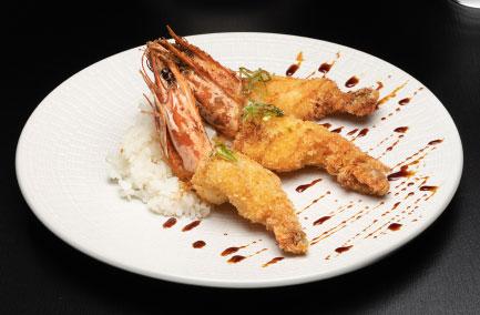 Trois gambas tempura servies dans une assiette blanche