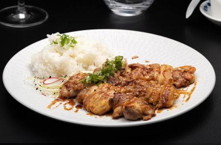 Trois brochettes de yakitori au poulet servies dans une assiette blanche
